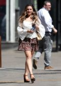 Kelly Brook wears a ruffled white top and layered miniskirt as she leaves Heart Radio station in London, UK