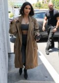 Kim Kardashian dons matching grey outfit with a trench coat while stopping by an art supply store in Los Angeles