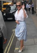 Kylie Minogue wears a stylish skirt and white blouse while visiting Kiss FM in London, UK