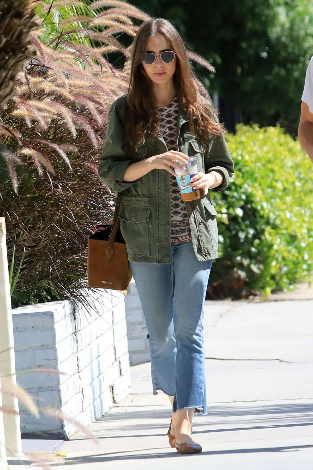 Lily Collins grabs lunch with a friend at Alfred's in West Hollywood, Los Angeles