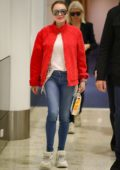 Lindsay Lohan stands out in a bright red jacket as she touches down at Sydney airport, Australia