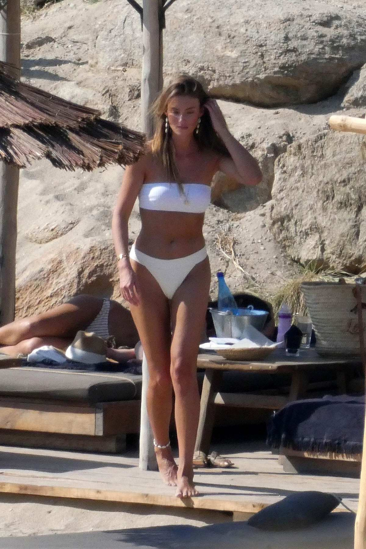 Lorena Rae seen wearing a white bandeau bikini while relaxing at the beach with her boyfriend in Mykonos, Greece