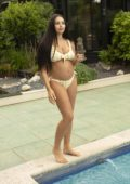 Marnie Simpson shows off her baby bump in yellow checkered bikini while relaxing by the pool in Cyprus