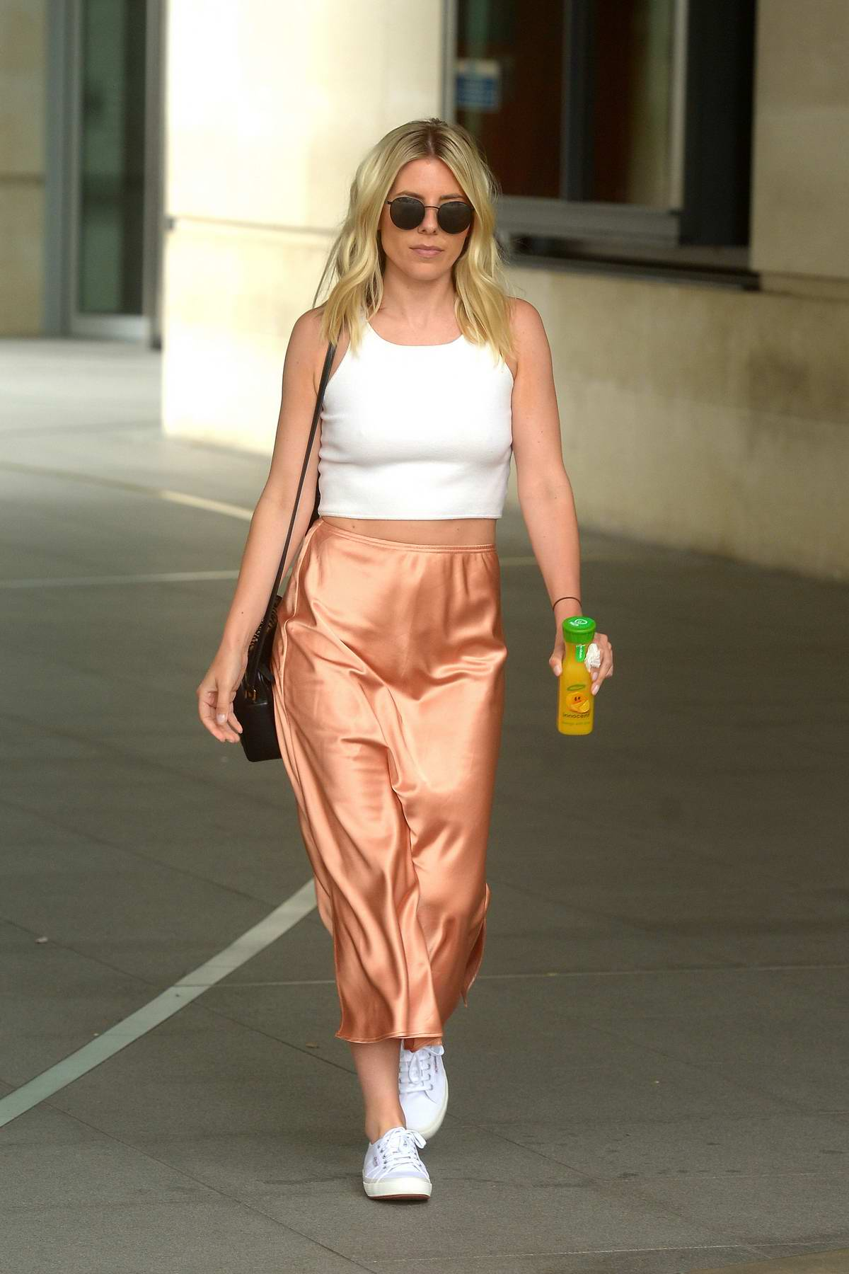 Mollie King dons a white crop top and blush colored skirt as she leaves BBC Radio One Studios in London, UK