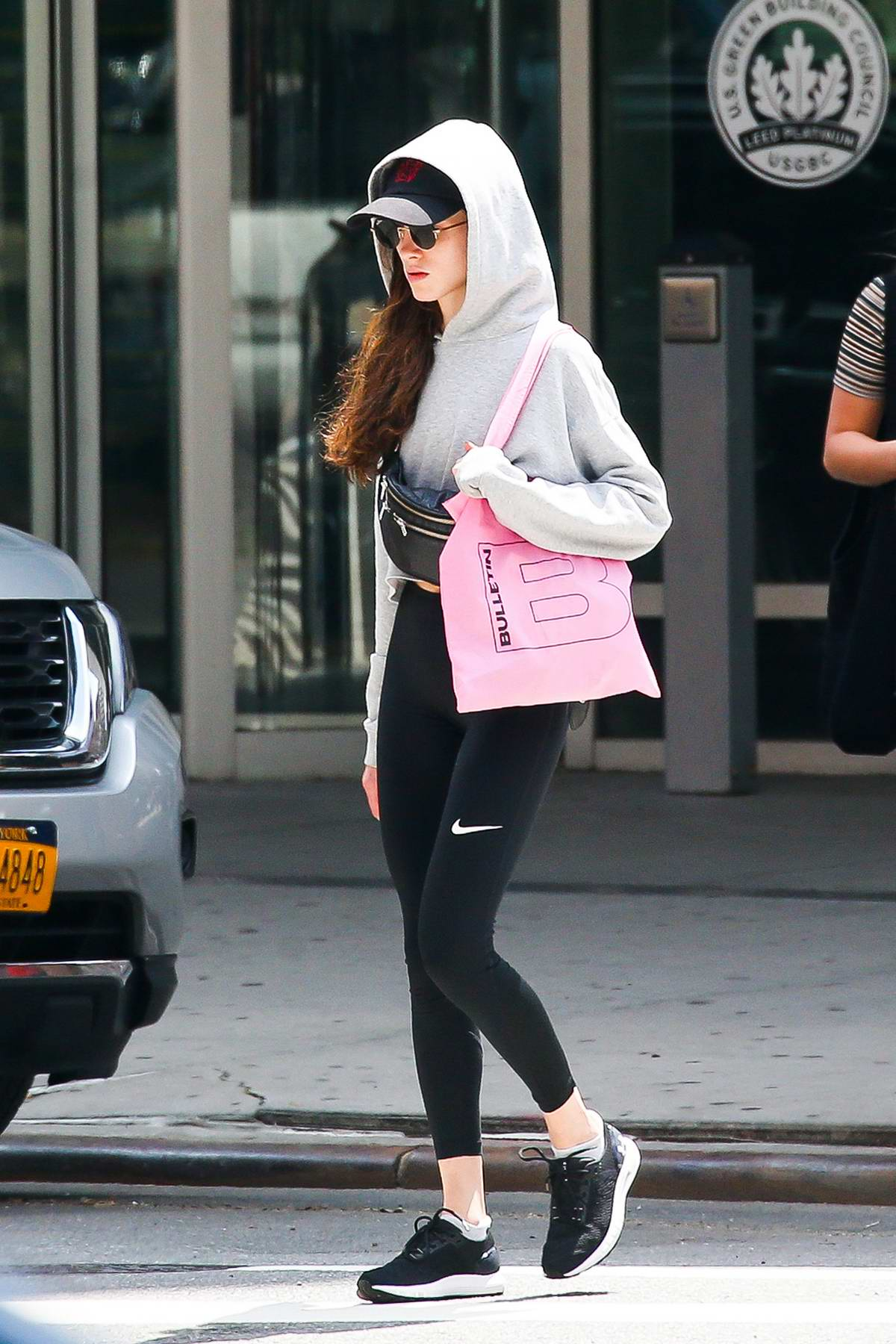Natalia Dyer goes incognito in a hat and hoodie paired with Nike leggings while out in New York City