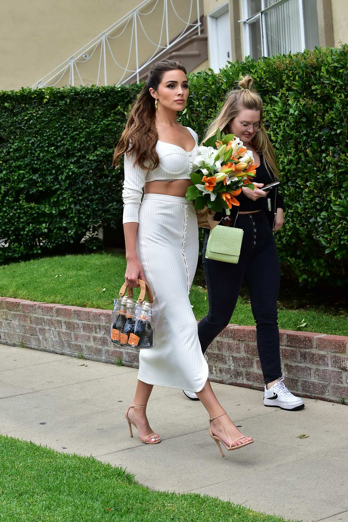 Olivia Culpo looks gorgeous in white as she steps out carrying a pack of wines and flowers in Los Angeles