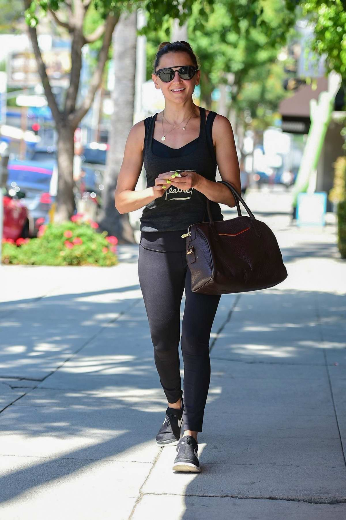 Rachael Leigh Cook sports a black tank top with matching leggings and Nike trainer as she leaves a gym in Studio City, Los Angeles