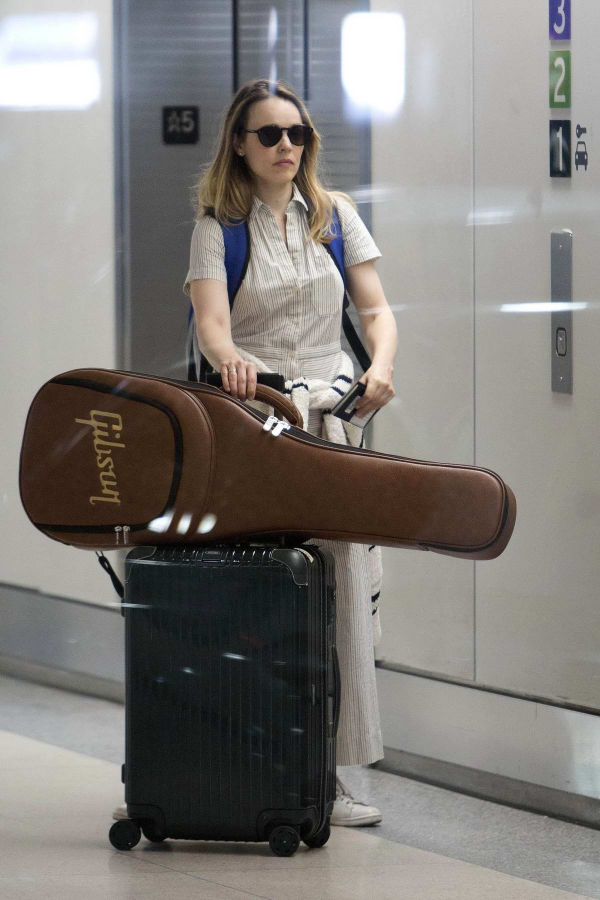 Rachel McAdams spotted in a striped jumpsuit while carrying a Gibson guitar along with her luggage as she touches down in Toronto, Canada