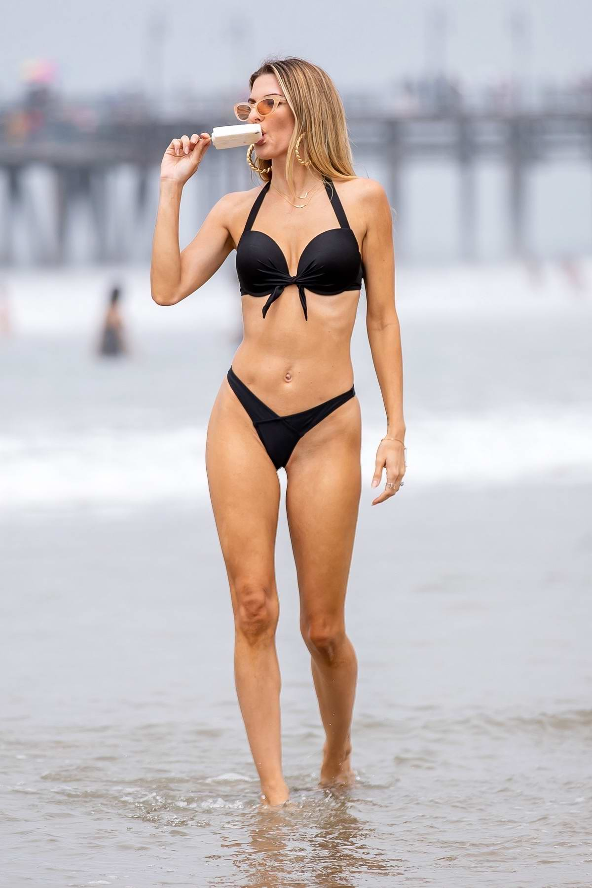 Rachel McCord cools off with an ice cream while she posing in a black bikini at the beach in Santa Monica, California