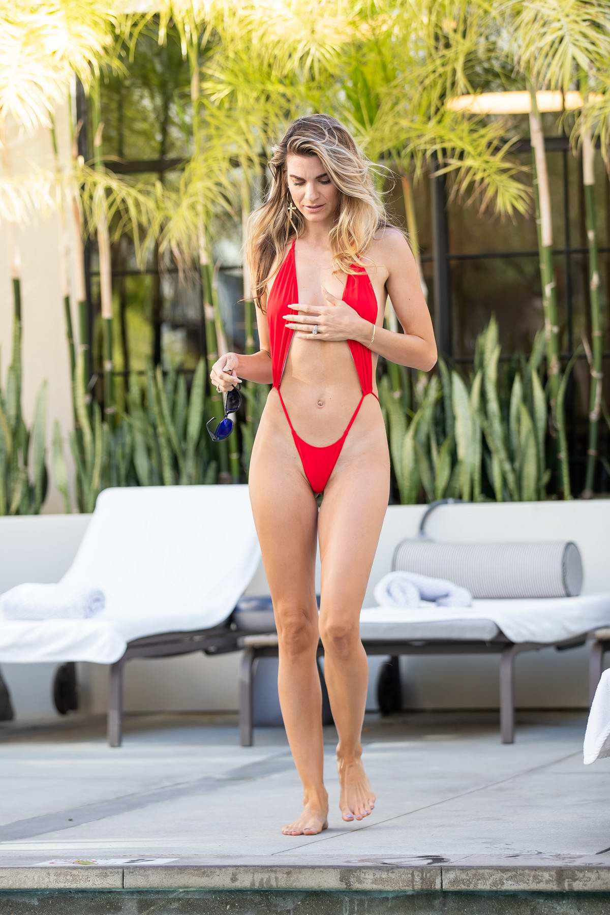 Rachel McCord sizzles in a red bikini while lounging by the pool with Christy Powers and Rick Schirmer at La Peer Hotel in West Hollywood, Los Angeles