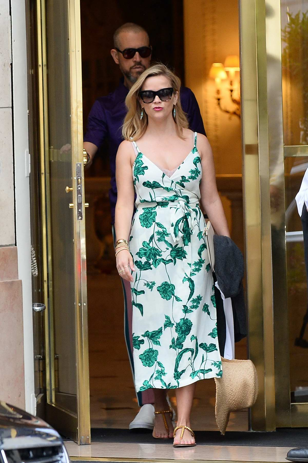 Reese Witherspoon looks lovely in a floral print dress as she leaves Bristol Hotel with husband Jim Toth in Paris, France