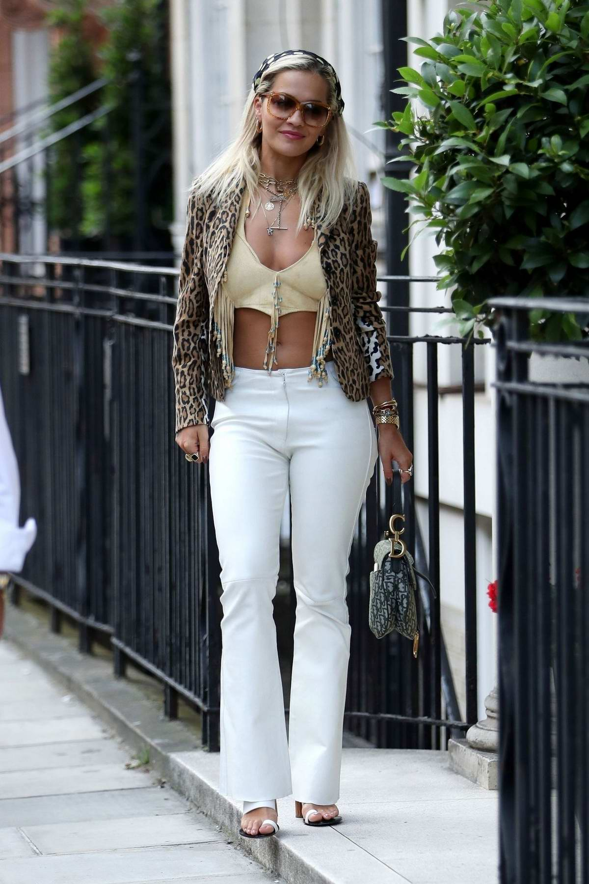 Rita Ora wears a yellow crop top, leopard print jacket and white trousers while heading to Scott's in London, UK
