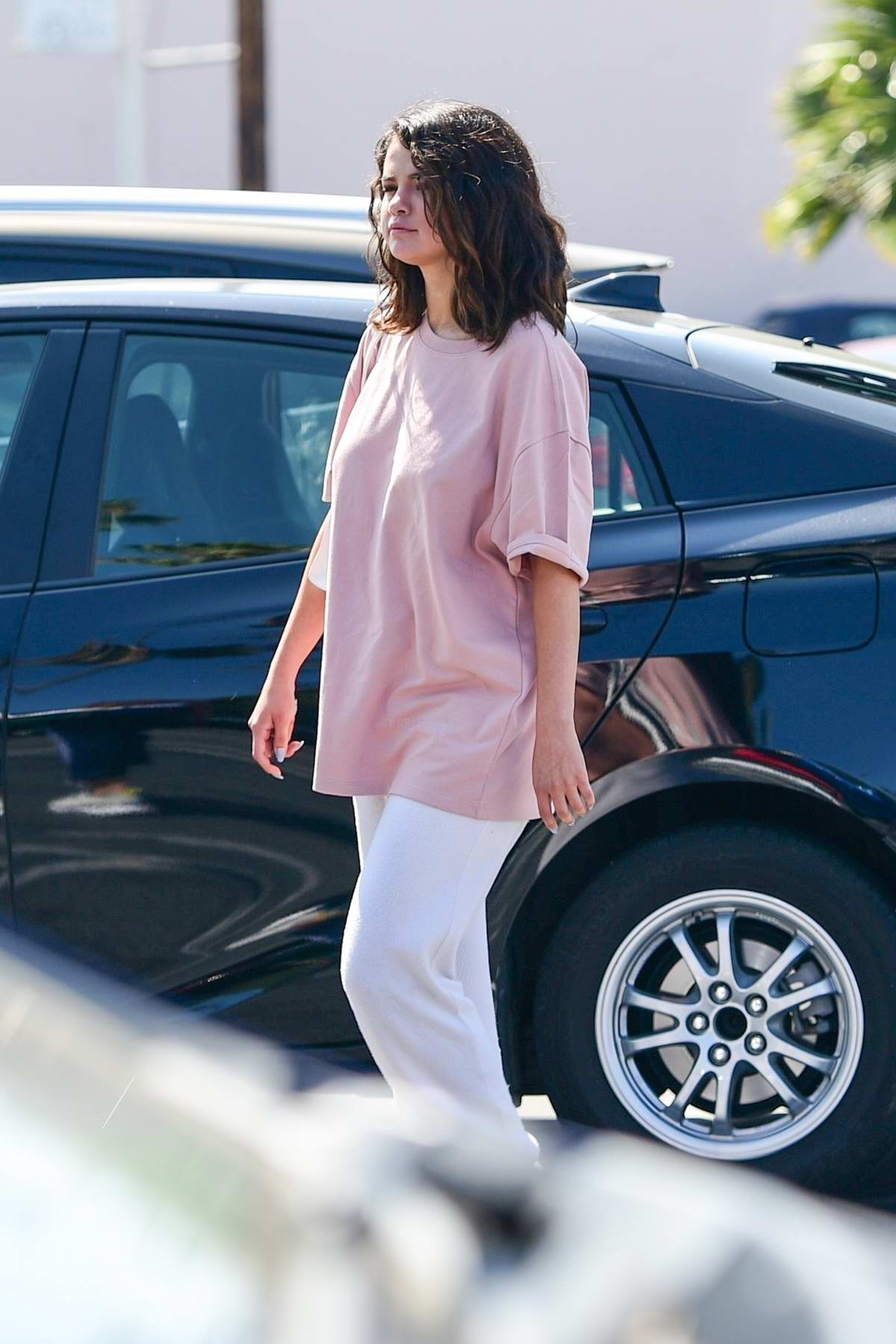 Selena Gomez wears an oversized pink t-shirt and white sweatpants during a shopping trip with friends in Los Angeles