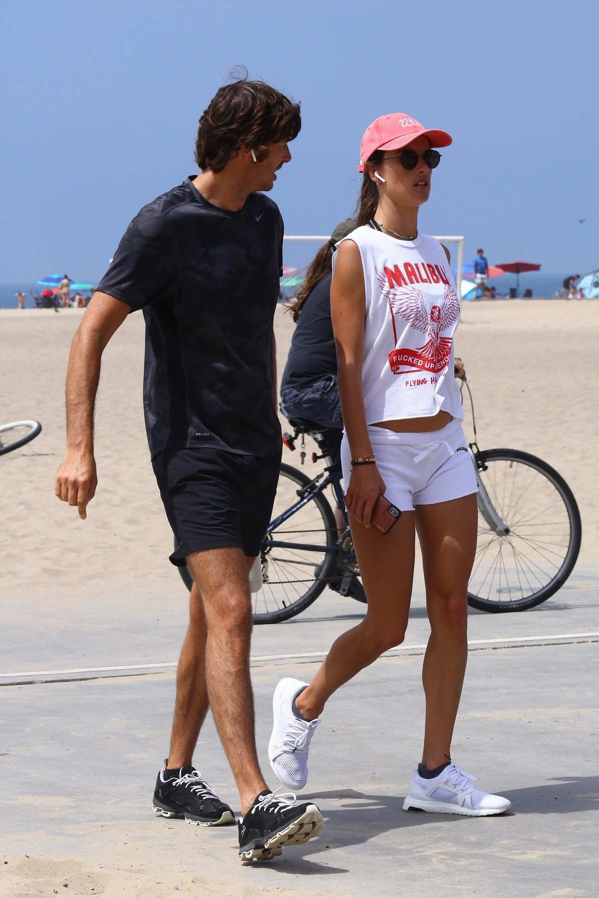 Alessandra Ambrosio sports white tank and shorts while out for a stroll with Nicolo Oddi at the beach in Santa Monica, California