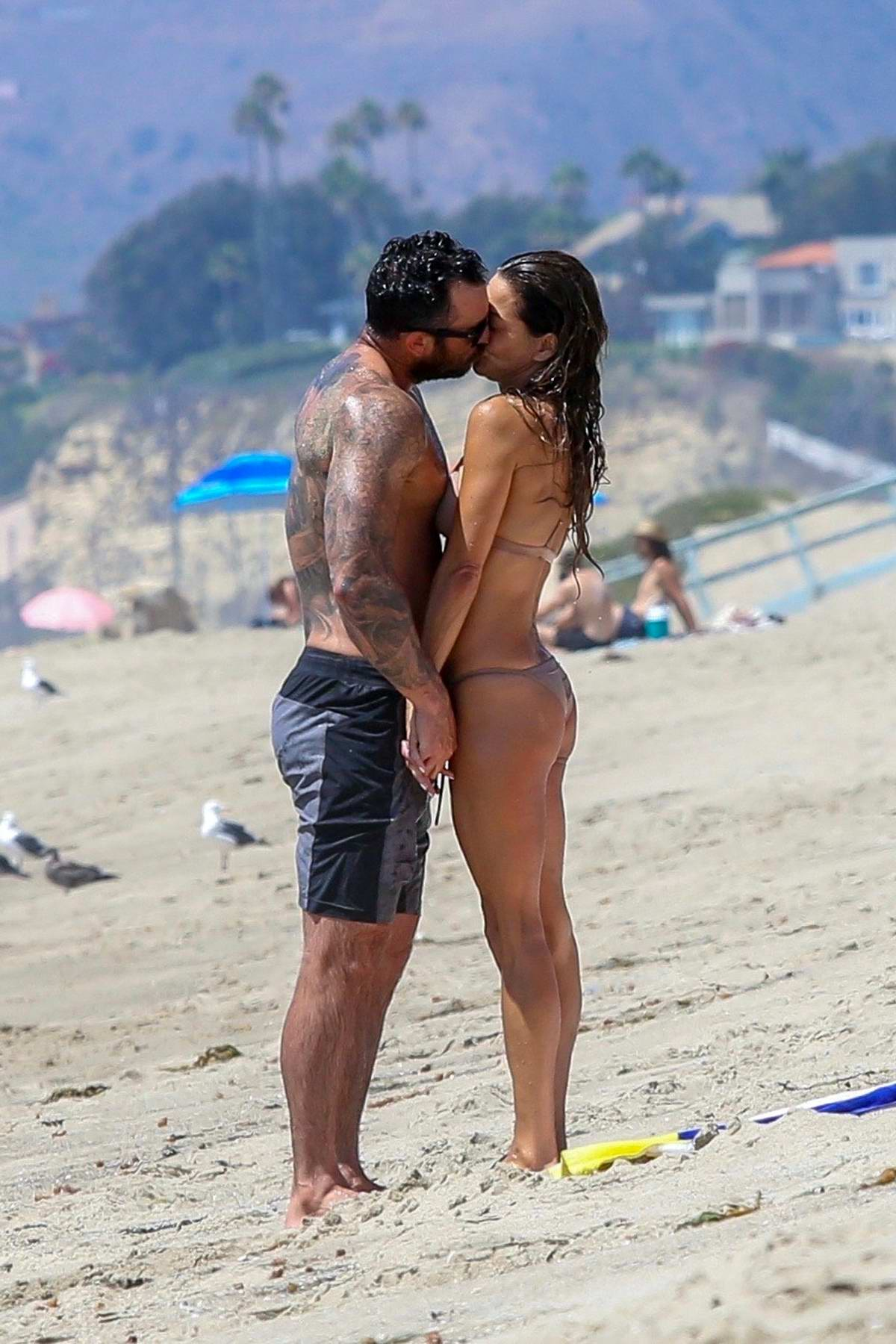 Brooke Burke spotted in a beige bikini as she packs on some PDA with her new boyfriend while on the beach in Malibu, California