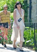 Daisy Lowe wears a low-cut semi sheer white lace dress as she takes her dog for a walk in London, UK