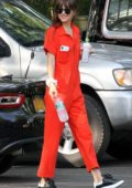 Dakota Johnson seen wearing an orange jumpsuit while out for lunch with Chris Martin in The Hampton's, New York