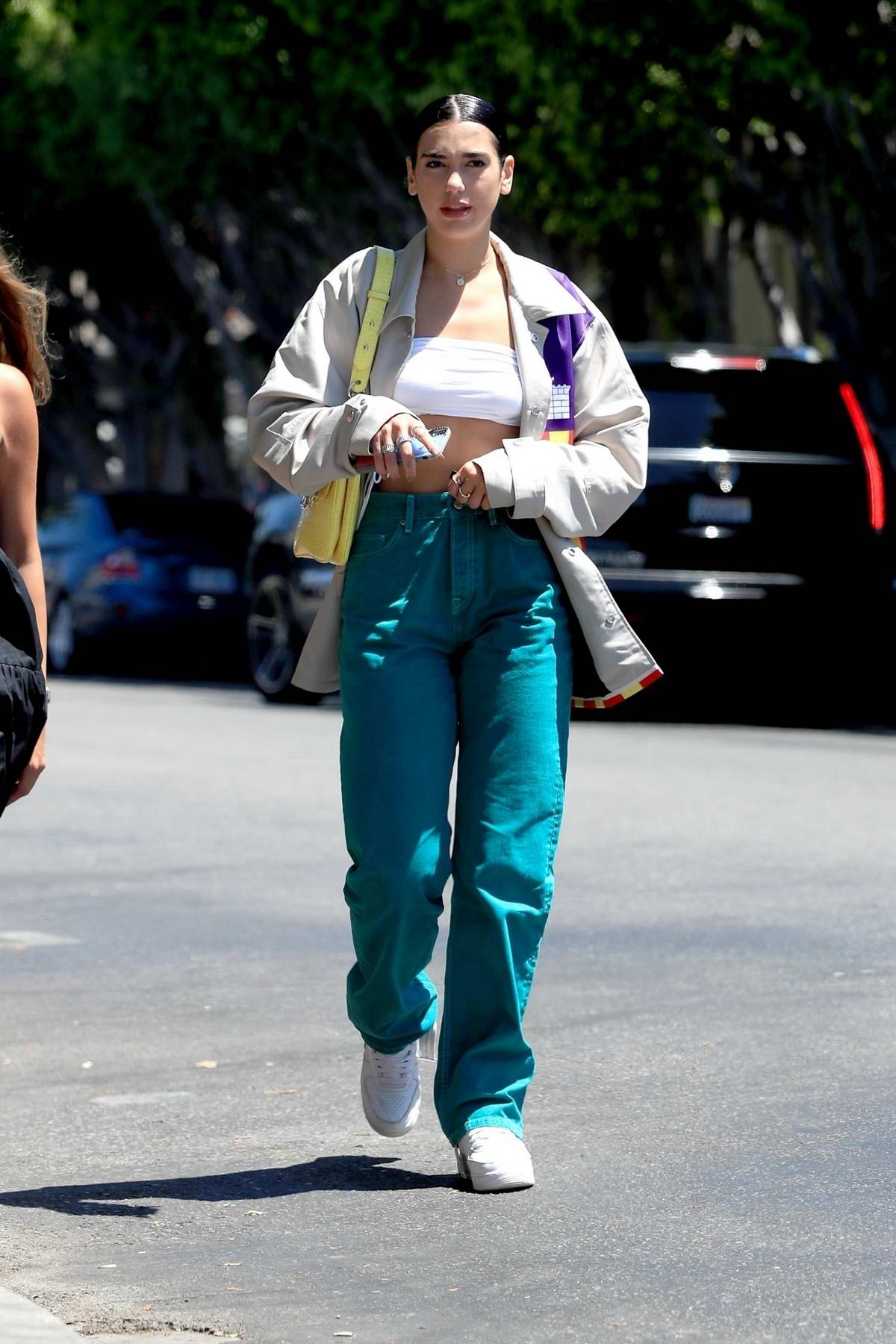 Dua Lipa rocks a white crop top and teal jeans with jacket while out for an iced drink at Alfred's in West Hollywood, Los Angeles