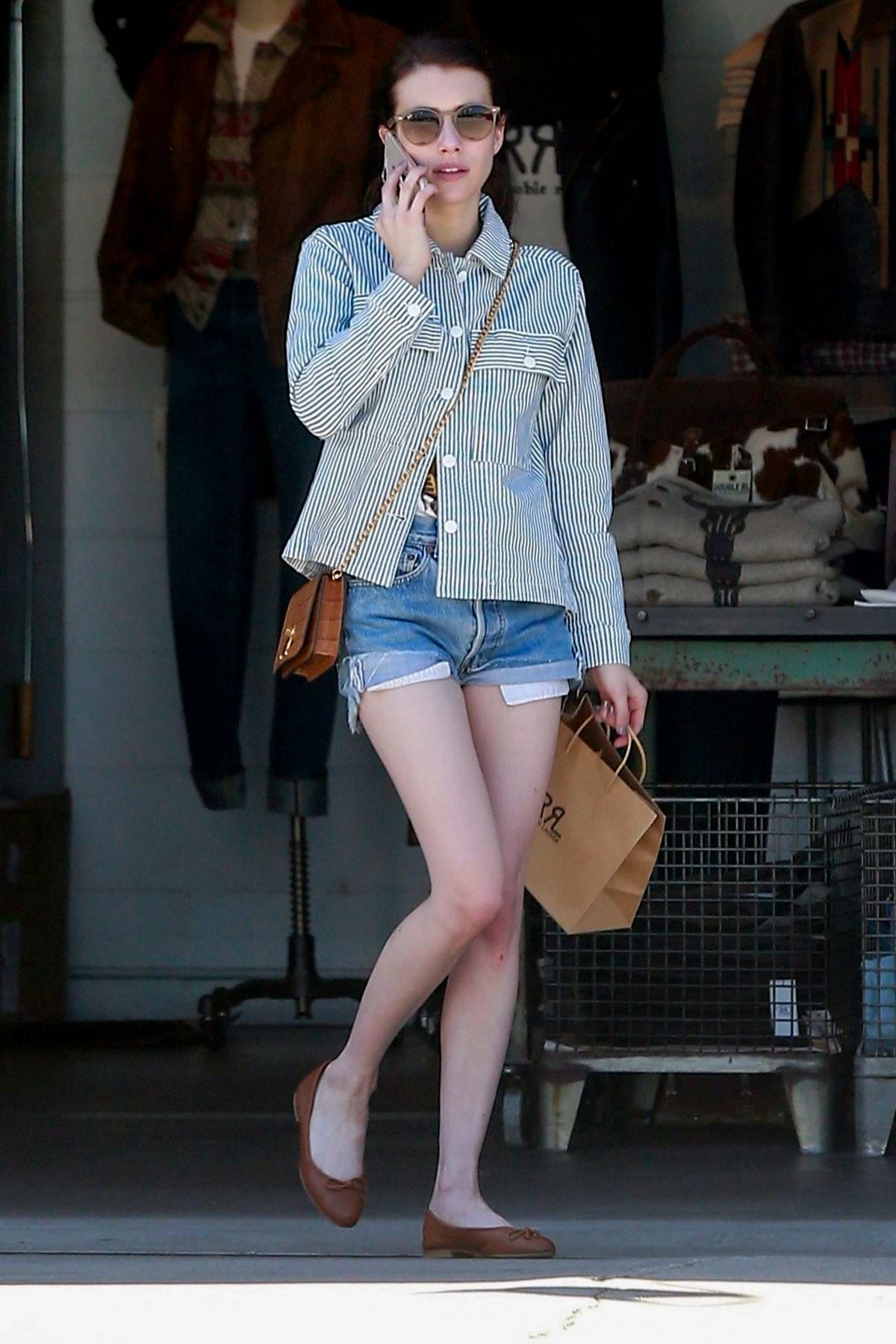Emma Roberts looks trendy in a striped shirt and denim shorts while out on a shopping trip in West Holywood, Los Angeles