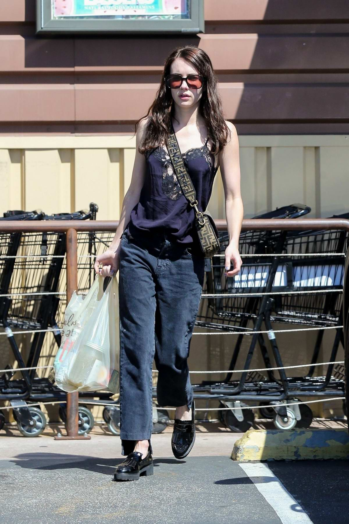 Emma Roberts wears a dark lace top and jeans as she stops by The Oaks Gourmet Market in Los Feliz, California