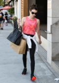 Emma Roberts wears a pink top and black leggings for a shopping trip to James Perse in Beverly Hills, Los Angeles