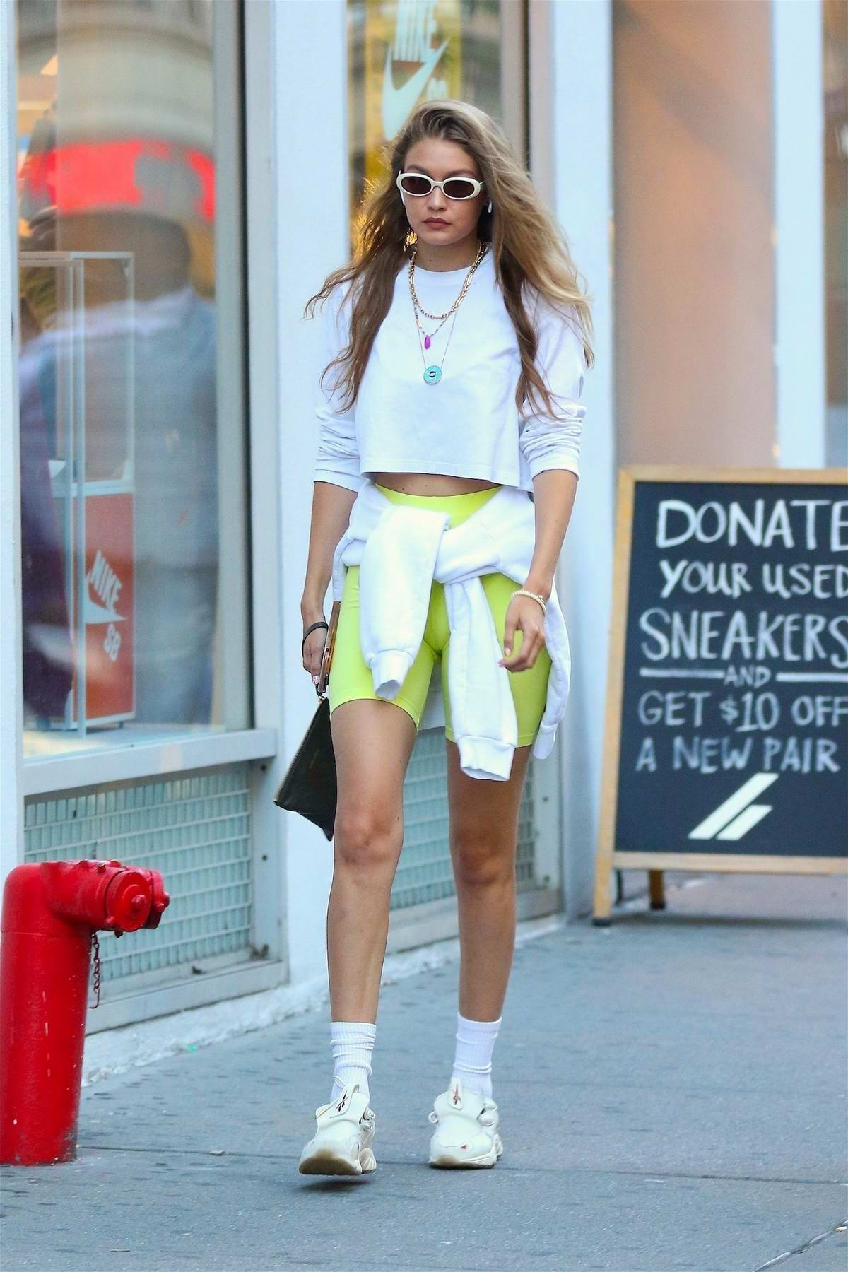 Gigi Hadid looks trendy in a white crop top and green legging shorts as she steps out in New York City