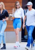 Gigi Hadid rocks a white crop top and blue legging shorts as she steps out in New York City