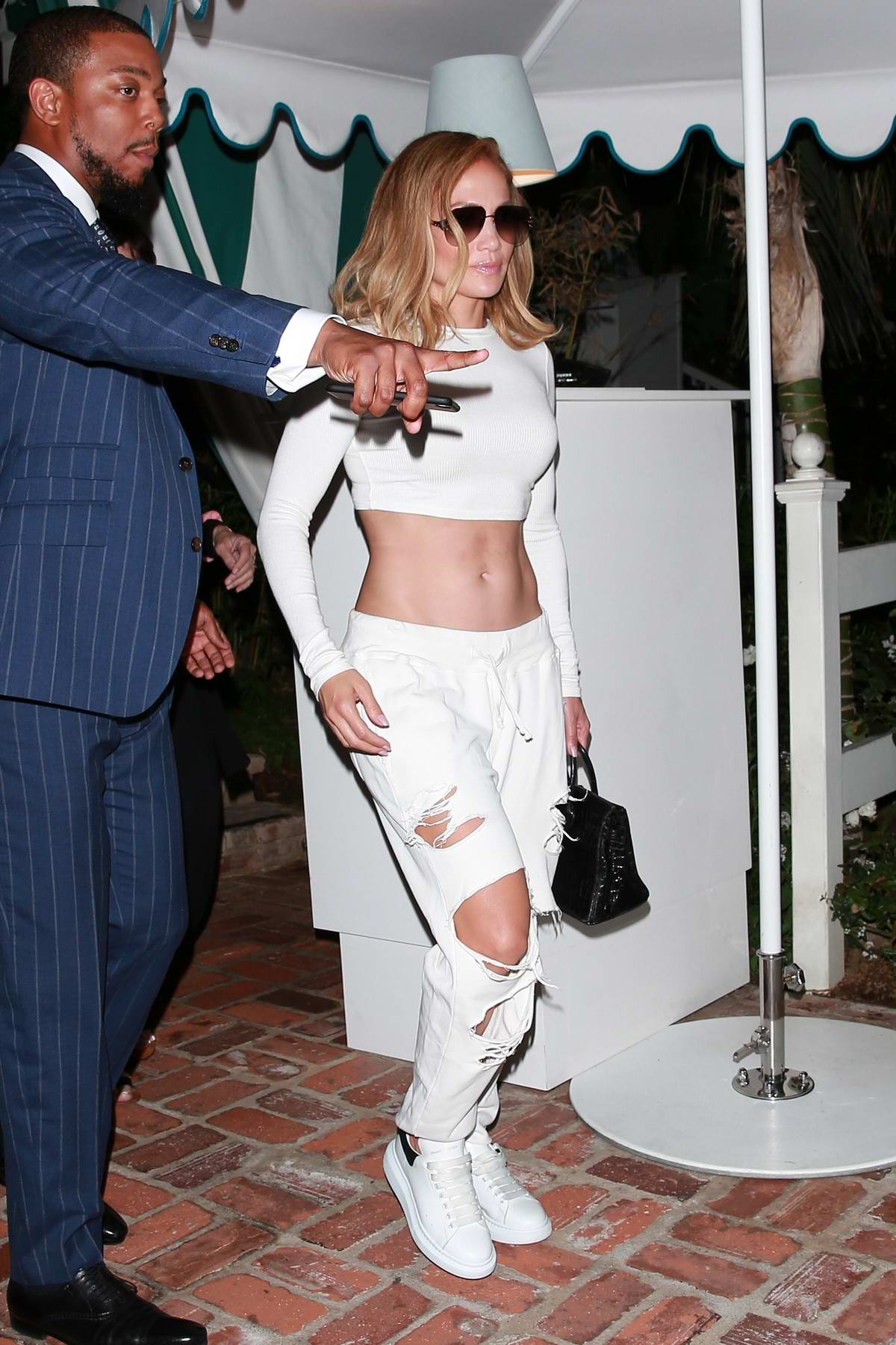 Jennifer Lopez bares her toned midriff in a white crop top while she meets up with Alex Rodriguez for dinner in Los Angeles