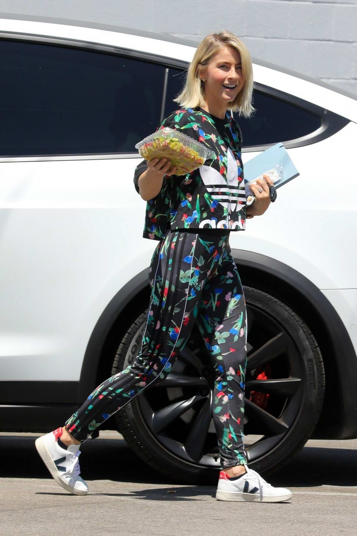 Julianne Hough wears a colorful Adidas top and matching leggings while arriving at a studio with a salad in Los Angeles