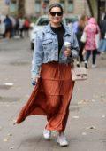 Kelly Brook looks great in ripped denim jacket and burnt orange skirt as she arrives at Global Radio Studios in London, UK