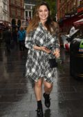 Kelly Brook wears a plaid dress with a smile as she leaves Global Radio Studios in London, UK