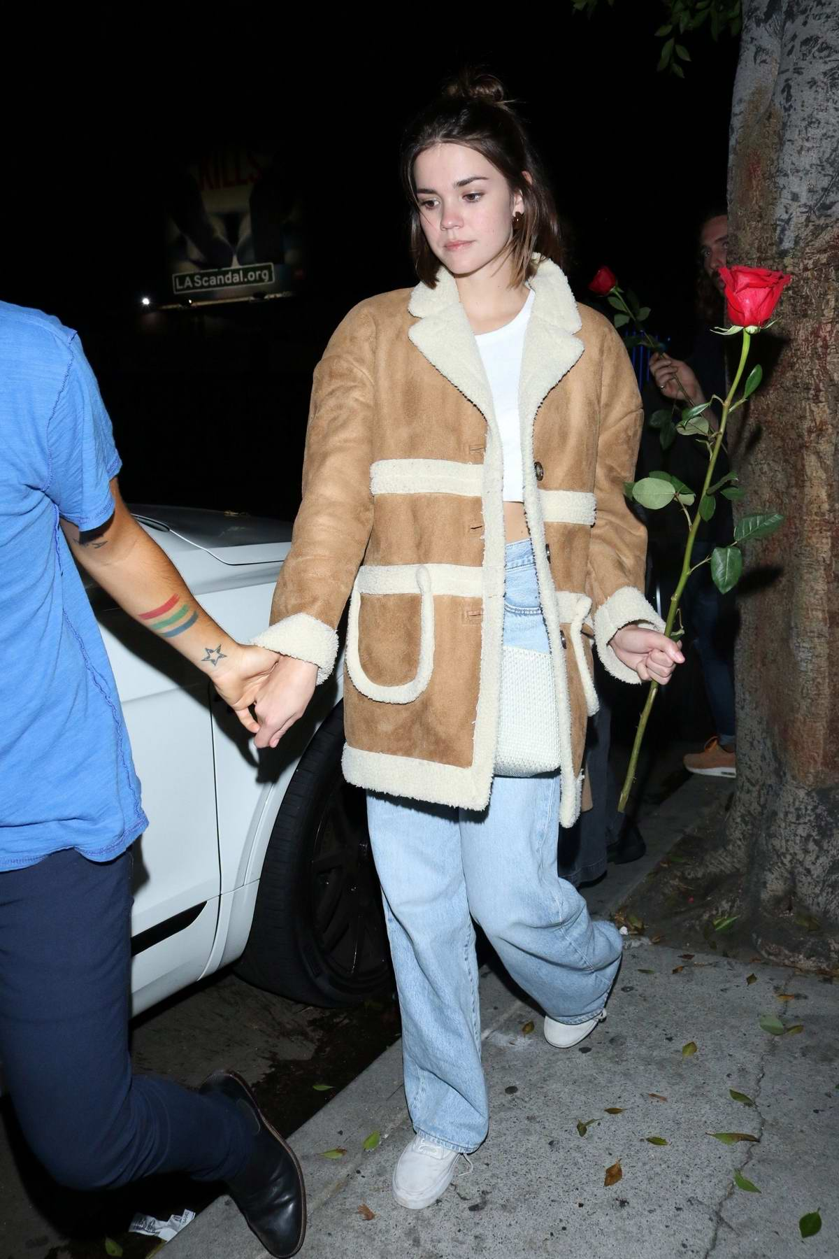 Maia Mitchell holds on to a red rose as she leaves the Warwick nightclub with Rudy Mancuso in Hollywood, California