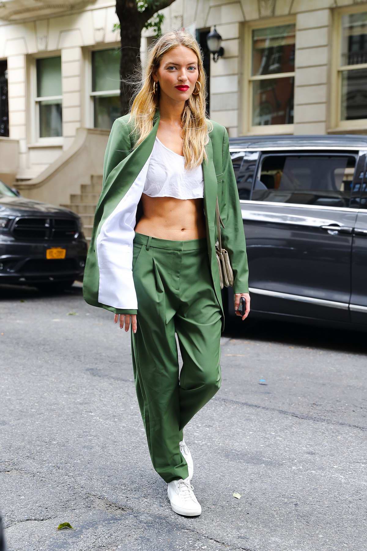 Martha Hunt shows off her perfect abs in a white crop top and green suit while out in New York City