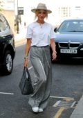 Megan McKenna steps out donning striped pants with a white top and straw hat in London, UK