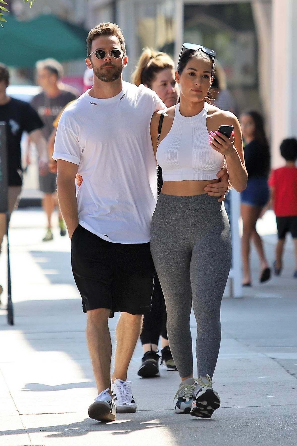Nikki Bella wears a white crop top and grey leggings for a lunch date with Artem Chigvintsev in Studio City, Los Angeles