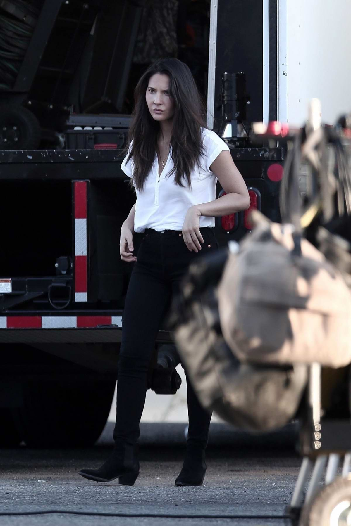 Olivia Munn seen wearing a white top and black jeans while on the set of her new movie 'Violet' in Los Angeles