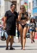 Rachel McCord wears a black crop top with bikini bottoms while enjoying a day out at Venice Beach, California