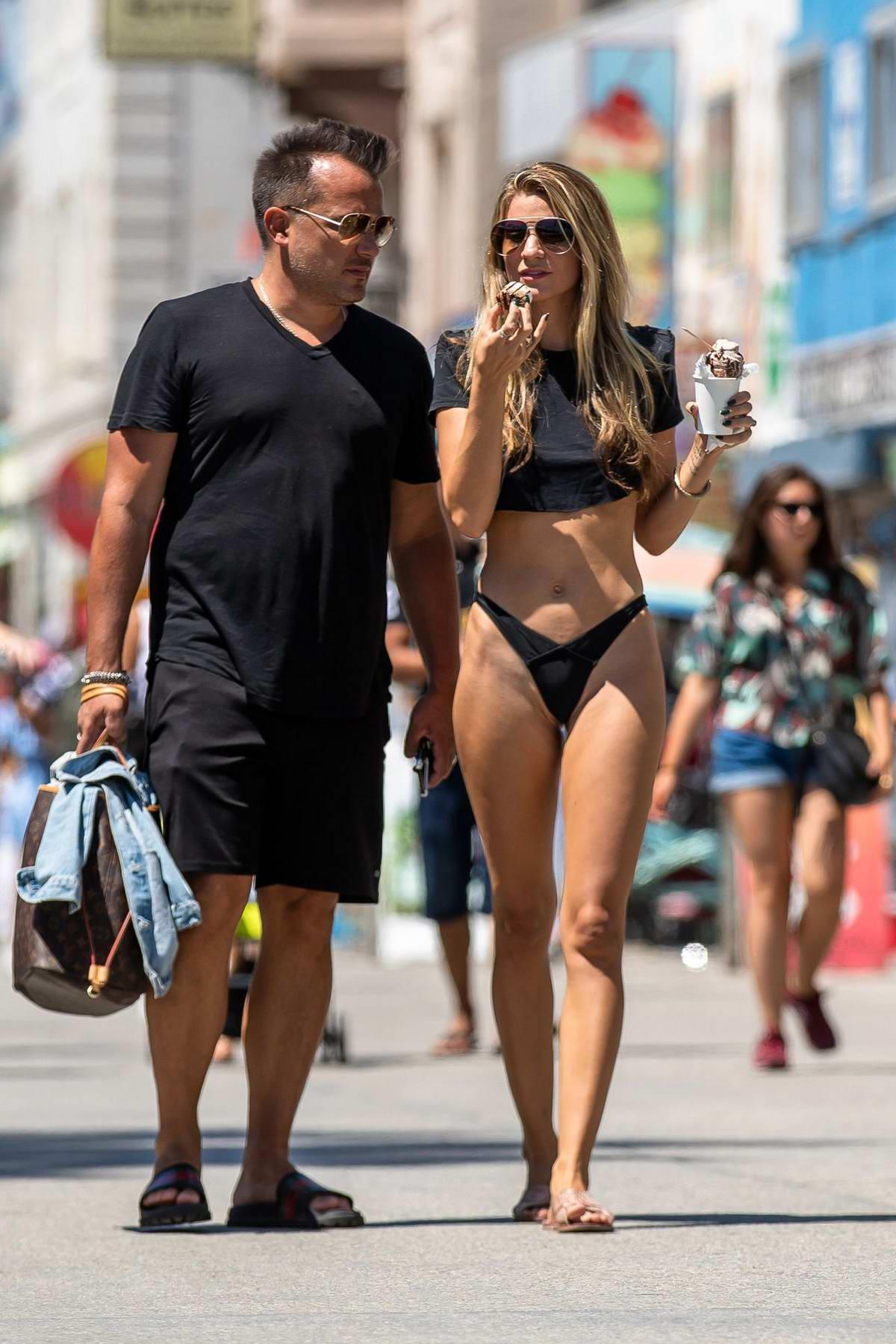 Rachel McCord wears a black crop top with bikini bottoms while enjoying a day out at Venice Beach, California