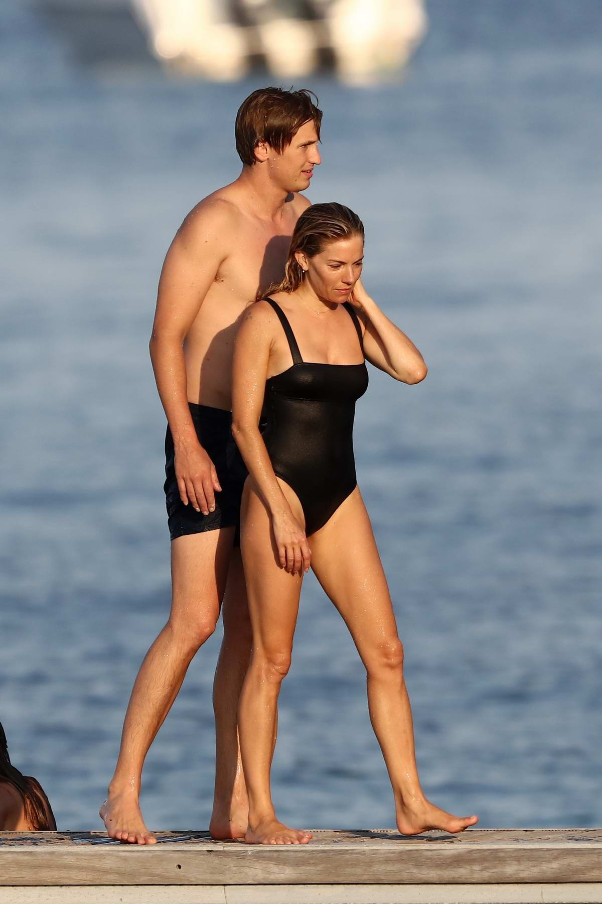 Sienna Miller dons a black swimsuit as she hits the beach with boyfriend Lucas Zwirner in Saint-Tropez, France