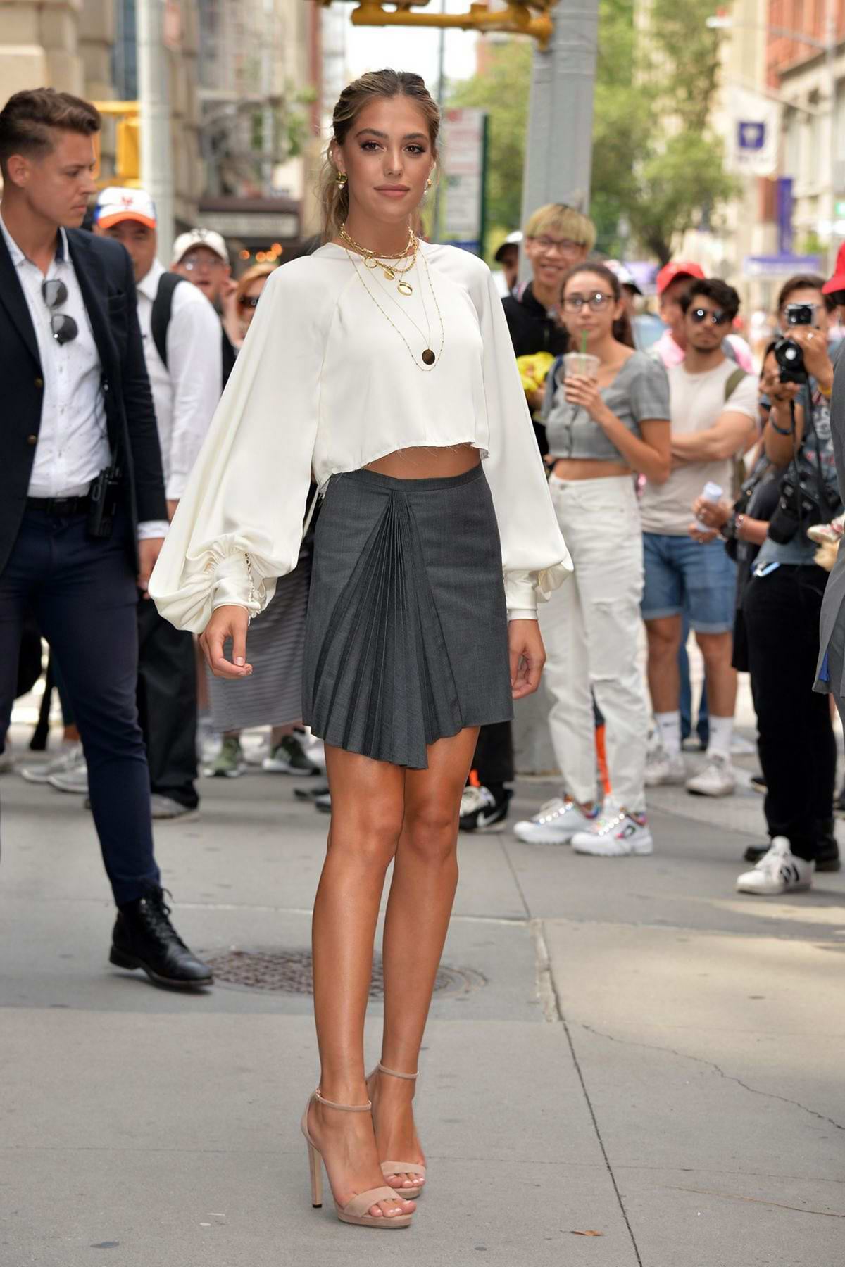 Sistine Stallone strikes a pose in a white crop top and grey skirt outside Build Studio in New York City