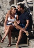 Sofia Richie wears a white crop top as she cuddles up with Soctt Disick while on vacation in Nerano, Italy