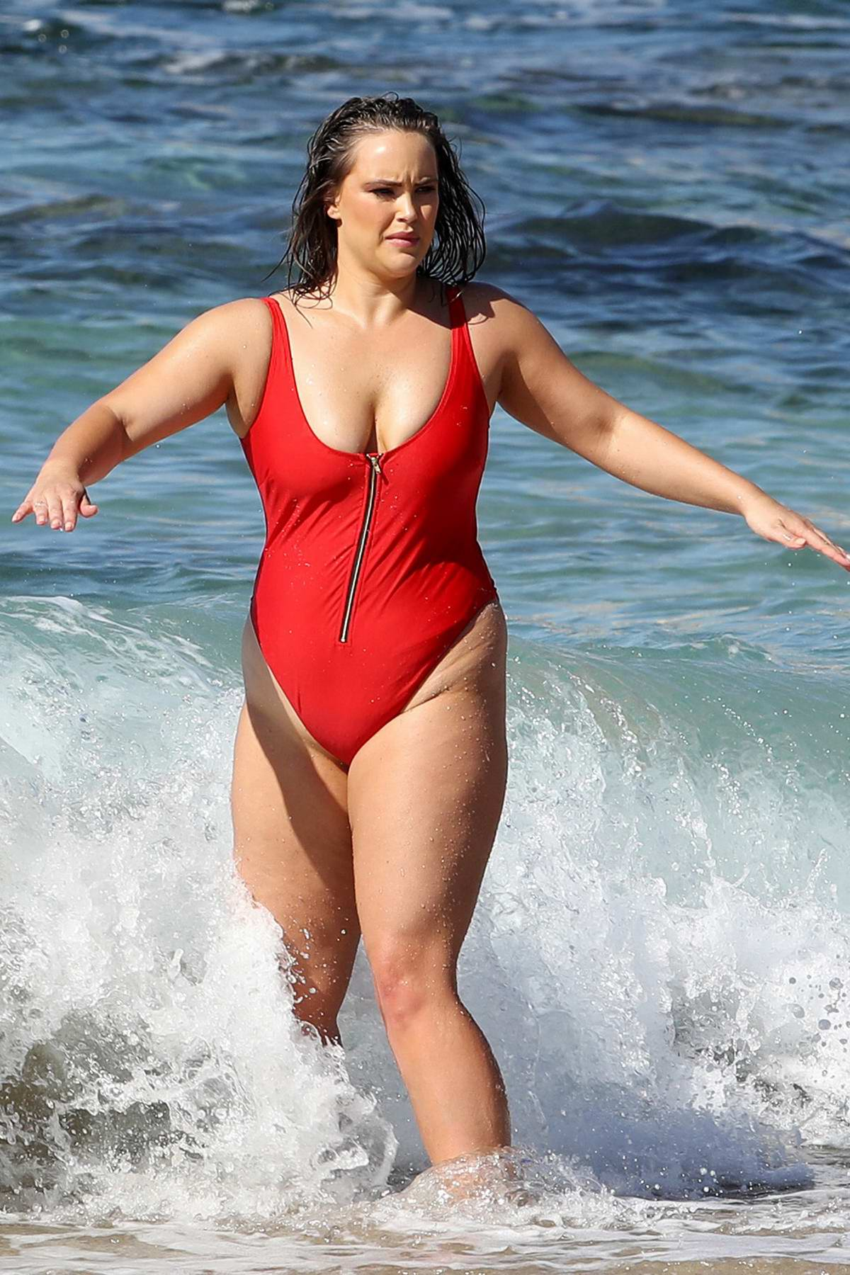 Sophia Brennan poses in a red swimsuit for a swimwear photoshoot at the beach in Sydney, Australia