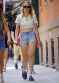 Sophie Turner looks cool and casual in denim shorts and yellow crop top while walking around with a friend in New York City