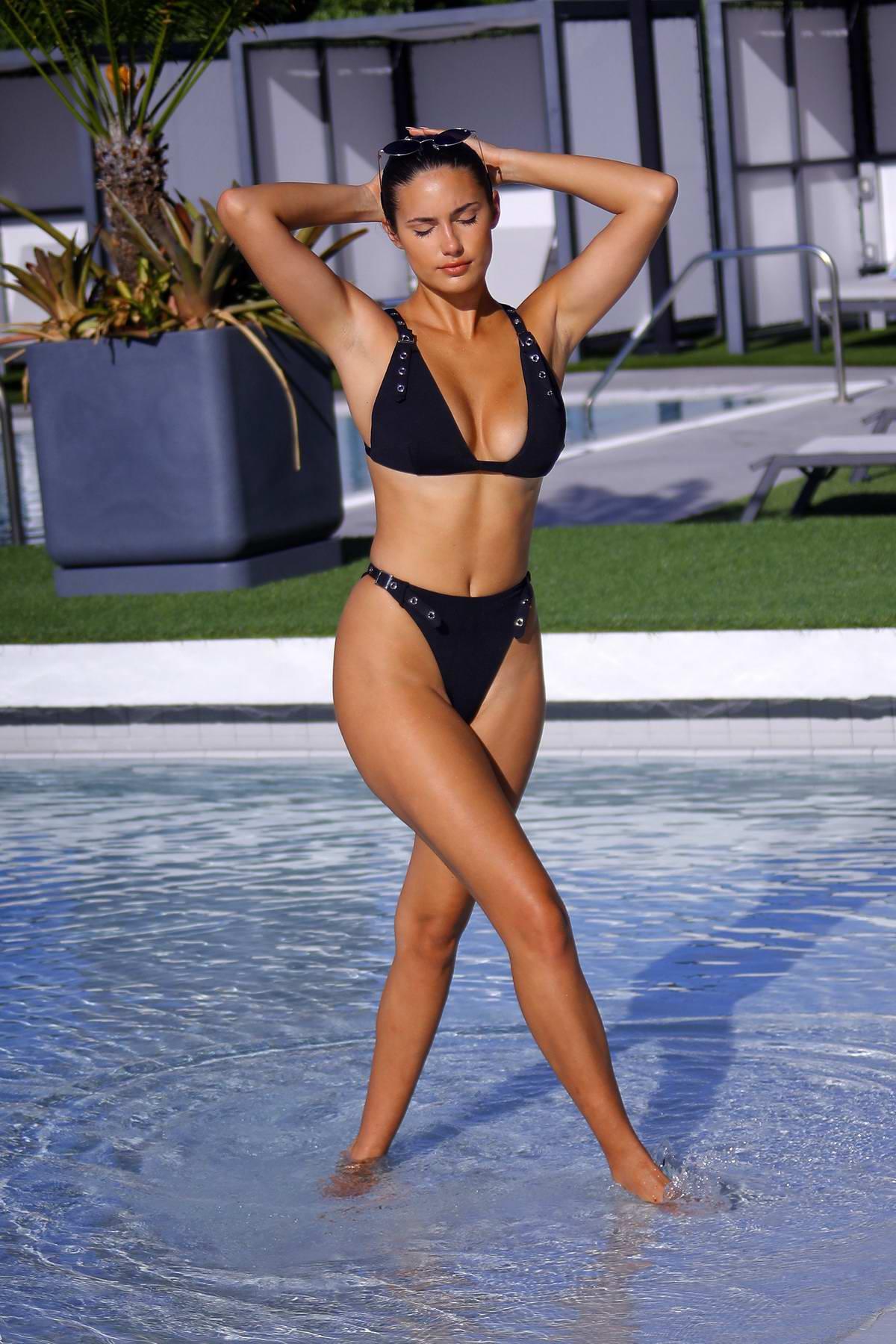 Tao Wickrath soaks up the sun in a black bikini while enjoying the pool at her hotel in Miami Beach, Florida