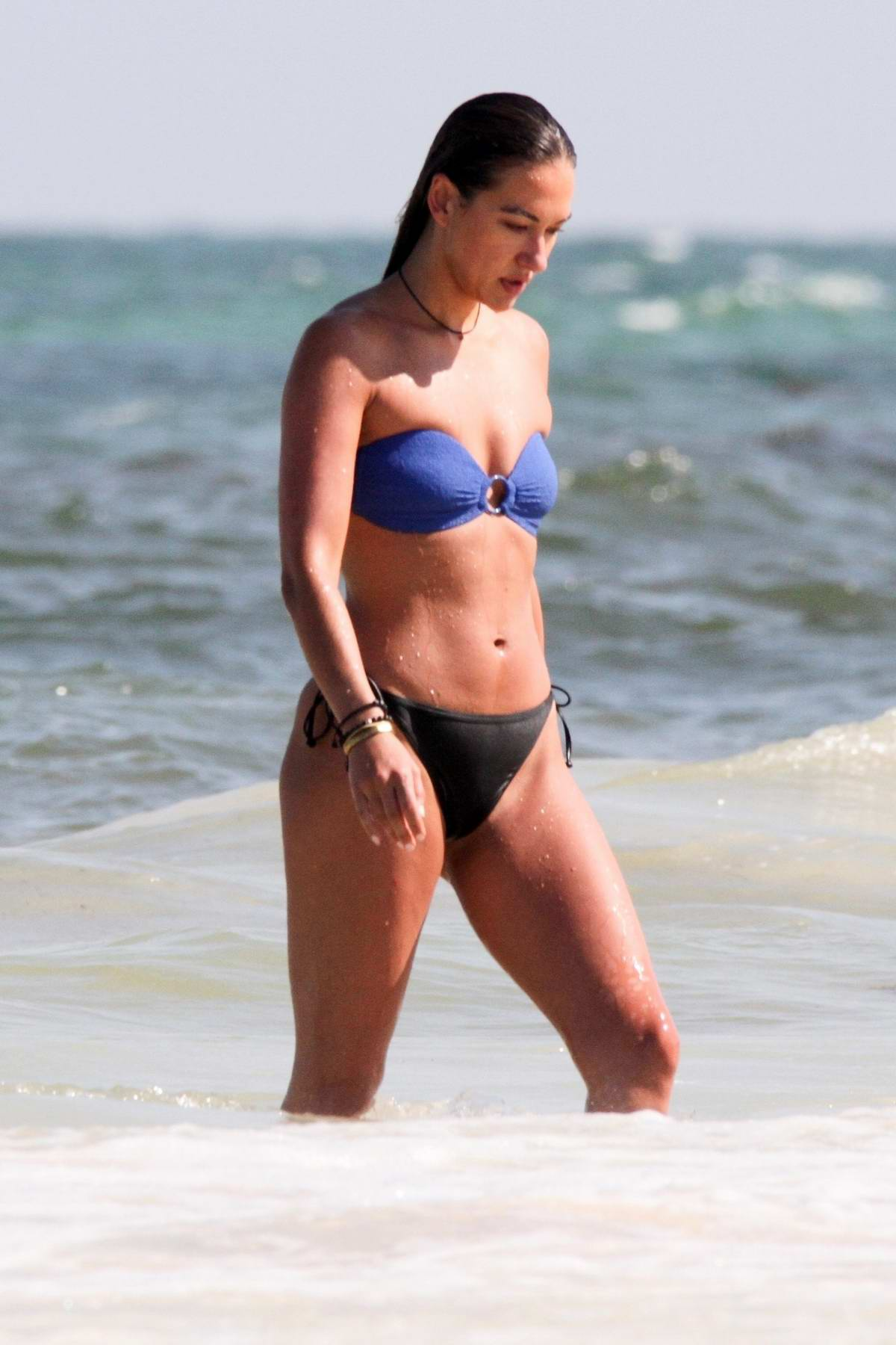 Tasya Teles shows off her beach body in a blue and black bikini as she goes for a swim while on vacation in Tulum, Mexico