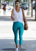 Alessandra Ambrosio wears a white top and aqua blue leggings as she steps out for a stroll in Brentwood, Los Angeles