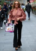 Amanda Holden wears a frilly peach top and black pants as she leaves Global Radio Studios in London, UK