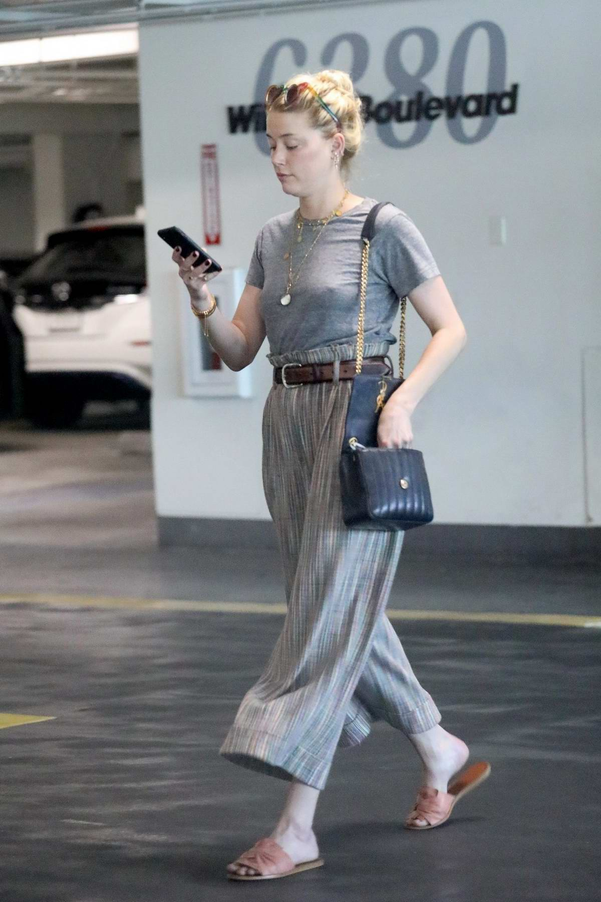 Amber Heard checks her messages after a meeting with lawyers on Wilshire Boulevard in Los Angeles