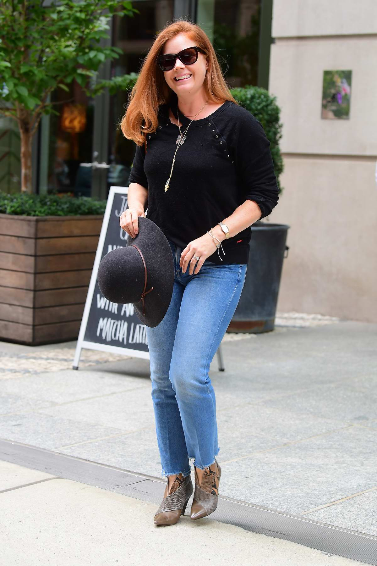 Amy Adams smiles for the camera as she checks out of her hotel in SoHo, New York City