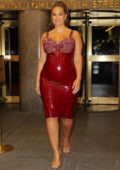 Ashley Graham shows off her baby bump in a form-fitting red dress as she leaves the Rainbow room in New York City